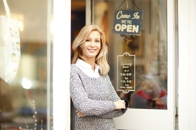 Portrait of designer woman standing in front of small vintage store