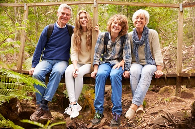 Grandparents and teens sit on bridge in forest