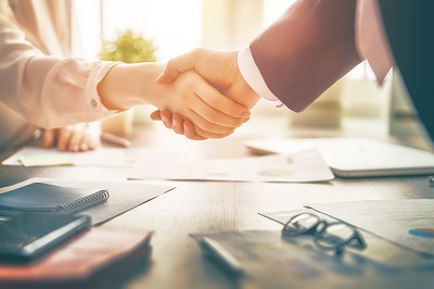 Man and woman are shaking hands in office
